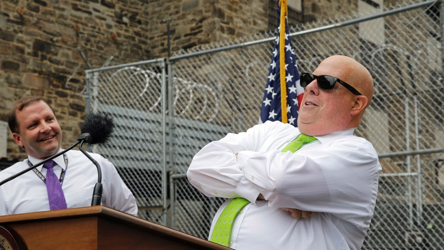 July 30, 2015: Maryland Gov. Larry Hogan, right, poses at Baltimore City Detention Center in Baltimore, at the end of a news conference to announce his plan to immediately shut down the jail.