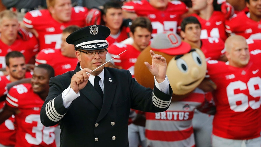 """Sept. 7, 2013: Ohio State University marching band director Jonathan Waters leads the band in """"Carmen Ohio"""" following an NCAA football game against San Diego State at Ohio Stadium in Columbus, Ohio."""
