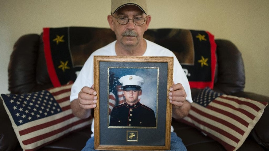 In this Saturday, July 25, 2015 photo Keith Wightman shows a frame picture of his son Lance Cpl. Brett Wightman at his home in Washington Court House, Ohio. Wightman was one of 14 Marines from Ohio-based Lima Company who were killed by an IED explosion in Iraq 10 years ago.