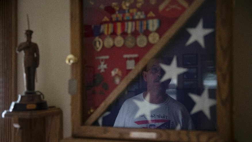 In this Saturday, July 25, 2015 photo Keith Wightman is reflected in a memorial case for his son Lance Cpl. Brett Wightman in Washington Court House, Ohio. Wightman was one of 14 Marines from Ohio-based Lima Company who were killed by an IED explosion in Iraq 10 years ago. (AP Photo/John Minchillo)