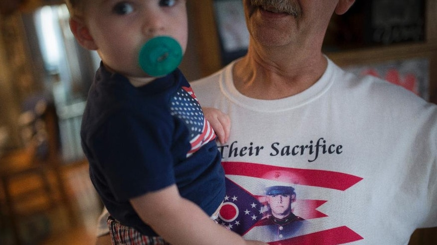 In this Saturday, July 25, 2015 photo Keith Wightman holds his grandson Kamden Garrison while wearing a shirt bearing the likeness of his son Lance Cpl. Brett Wightman at his home in Washington Court House, Ohio. Wightman was one of 14 Marines from Ohio-based Lima Company who were killed by an IED explosion in Iraq 10 years ago. (AP Photo/John Minchillo)