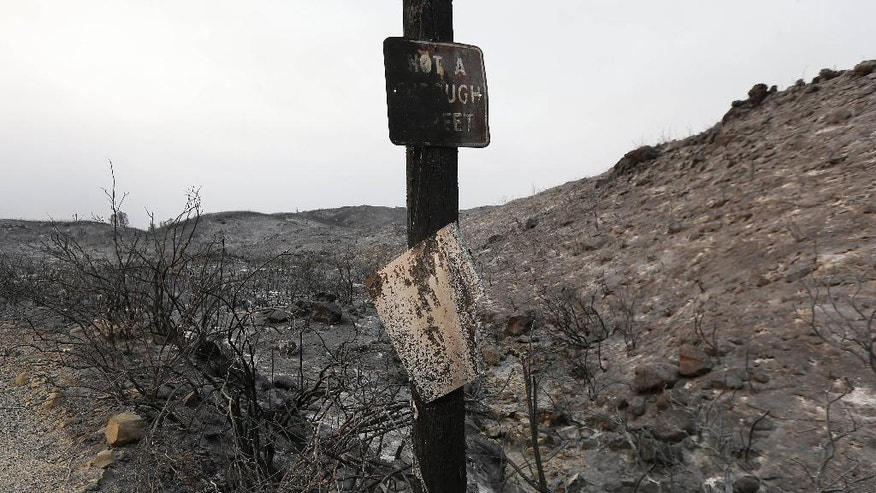 Burned signs are shown on a road near Lower Lake, Calif., Friday, July 31, 2015. A series of wildfires were intensified by dry vegetation, triple-digit temperatures and gusting winds. (AP Photo/Jeff Chiu)