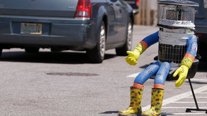 July 17, 2015: A car drives by HitchBOT, a hitchhiking robot in Marblehead, Mass. The Canadian researchers who created hitchBOT as a social experiment say someone in Philadelphia damaged the robot beyond repair on ending its brief American tour. (AP)