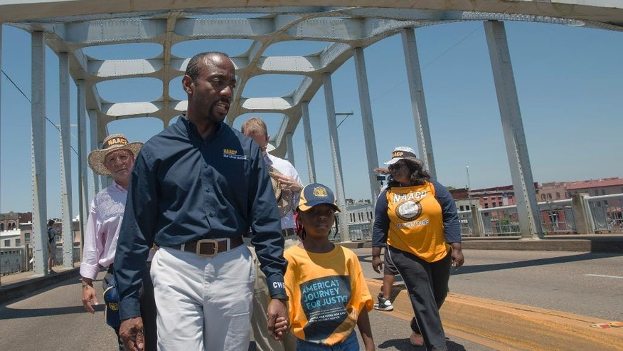 """Cornell William Brooks, NAACP president, holds the hand of Rachel Quarterman, 7, while leading the """"America's Journey for Justice March"""" organized by the NAACP on Saturday, Aug. 1, 2015, in Selma, Ala. The 860 mile relay march is planned to go from Selma to Washington D.C. over the course of 40 days. (Albert Cesare/Montgomery Advertiser via AP)"""