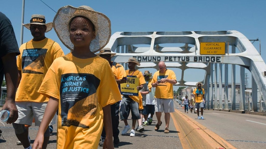 """Velivia Peterson, 8, walks with others across the Edmund Pettus Bridge during the start of the """"America's Journey for Justice March"""" organized by the NAACP on Saturday, Aug. 1, 2015, in Selma, Ala. The 860 mile relay march is planned to go from Selma to Washington D.C. over the course of 40 days. (Albert Cesare/Montgomery Advertiser via AP)"""