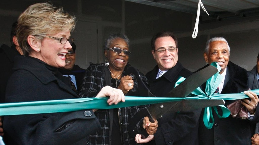 FILE - In a Jan. 18, 2010 file photo, Sallie Sanders, second from left, is helped by, from left, Michigan Gov. Jennifer Granholm, Wayne County Executive Robert Ficano and Judge Damon Keith, with a ribbon cutting outside her new house in Hamtramck, Mich., near Detroit. Keith, now 93, has ordered taxpayers in Hamtramck to pay up as a way to end a housing discrimination case that has been in federal court for more than 40 years. (AP Photo/Carlos Osorio, File)