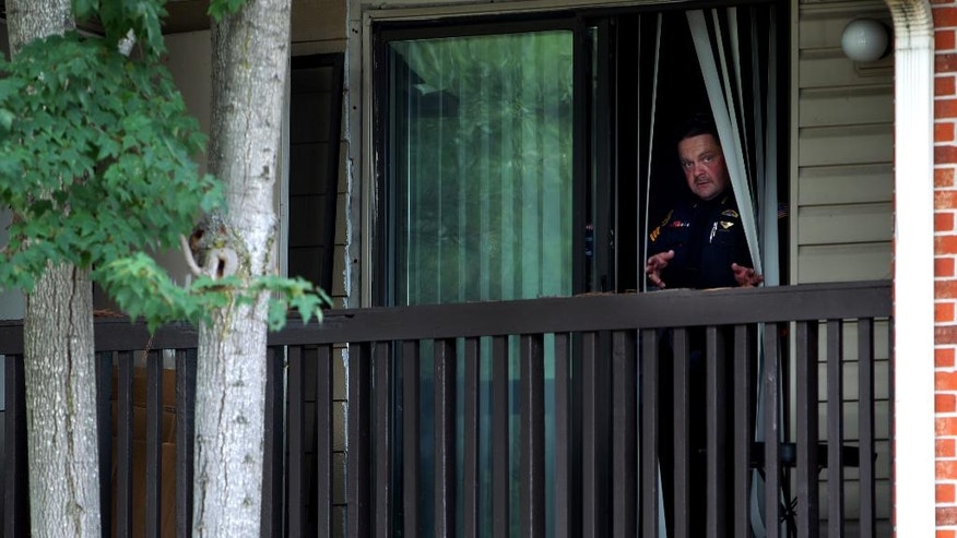 A Memphis Police officer looks out from an apartment balcony after a standoff  near the area where Police Officer Sean Bolton was fatally shot Saturday, Sunday, Aug. 2, 2015, in Memphis, Tenn.  (Mike Brown/The Commercial Appeal via AP)
