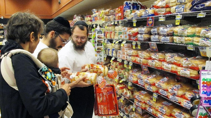 In this July 27, 2015 photo, orthodox Jewish rabbis Dovid Lepkivker, right, and Eli Chaikin, center, inspect packages of bagels with Mary Semple, left, and her grandson Levi Weitner in a grocery store in Helena, Mont. Lepkivker and Chaikin are on a mission to reach as many Montana Jews as they can in a month to teach them how to keep kosher. (AP Photo/Matt Volz)