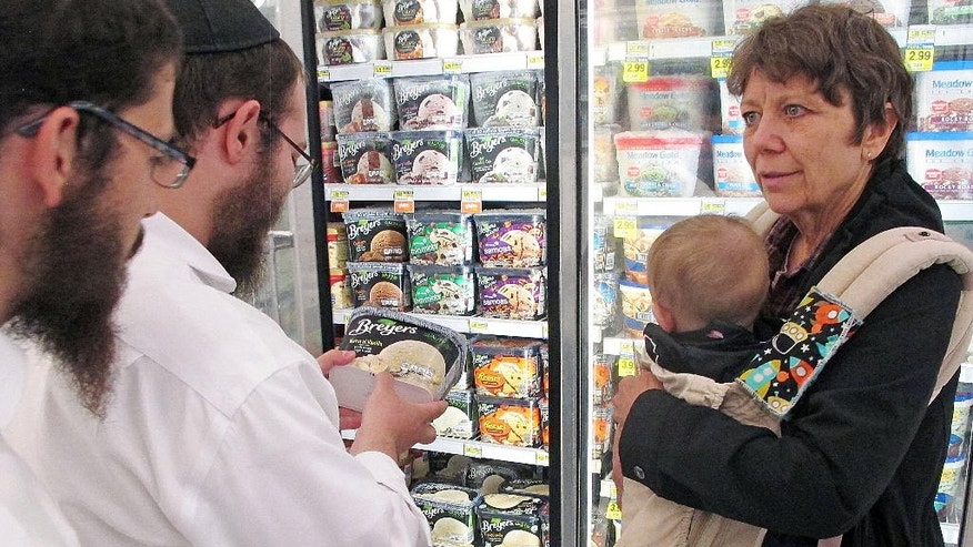 In this July 27, 2015 photo, orthodox Jewish rabbi Dovid Lepkivker, center, examines a container of Breyer's ice cream, which happens to be kosher, as fellow rabbi Eli Chaikin, left, and Mary Semple look on in Helena, Mont. Lepkivker and Chaikin are on a mission to reach as many Montana Jews as they can in a month to teach them how to keep kosher. (AP Photo/Matt Volz)