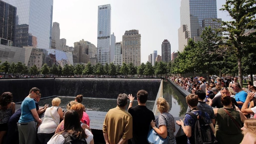 FILE - In this Aug. 8, 2014 file photo, visitors to the Sept. 11 memorial view one of the two reflecting pools in New York. A tourist from Texas was arrested on Saturday Aug. 1, 2015 on charges she was packing two loaded handguns at the Sept. 11 memorial in New York City, authorities said. According to a criminal complaint, Elizabeth Enderli was visiting the site  when she informed a police officer she had the weapons in her backpack. She was charged with criminal possession of a weapon before being released Sunday. Acording to friends, the 31-year-old military veteran has a permit to carry weapons in her home state and mistakenly believed the permit covered her visit to New York from the Houston area. (AP Photo/Mark Lennihan, File)