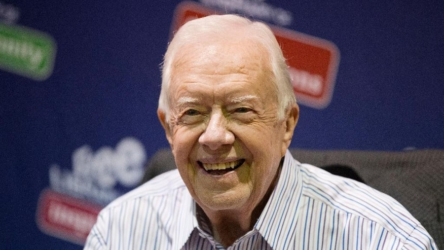 """FILE - In this July 10, 2015, file photo, former President Jimmy Carter poses for photographs at an event for his new book """"A Full Life: Reflections at Ninety at the Free Library in Philadelphia."""