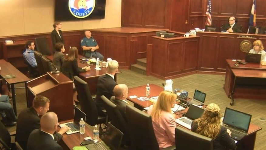 In this image made from Colorado Judicial Department video, James Holmes, top left in blue shirt, watches as defense attorney Kristen Nelson, second from top left speaks with Judge Carlos A. Samour, Jr., top right, after his reading of the jury's sentencing verdict in the Colorado theater shooting trial in Centennial, Colo., on Monday, Aug. 3, 2015. The jury declined to rule out the death penalty as the sentencing process continues. (Colorado Judicial Department via AP, Pool)