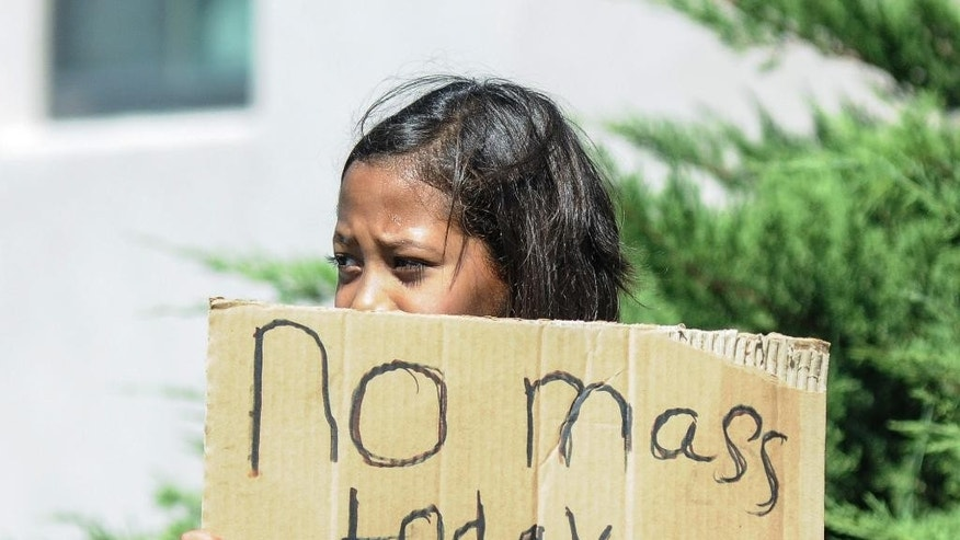 Aaliyah Doninguez, 11, stands on N. Alameda Boulevard on Sunday, Aug. 2, 2015, in Las Cruces, N.M., advising parishioners that Holy Cross Catholic Church mass is canceled. Churchgoers were left shaken during Sunday morning services after authorities say explosions occurred less than 30 minutes apart outside two Las Cruces churches. (Robin Zielinski/The Las Cruces Sun-News via AP) MANDATORY CREDIT