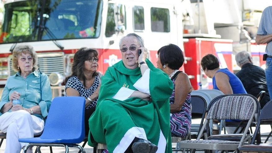 While waiting in a staging area, Holy Cross Catholic Church Pastor John Anderson tries to get in touch with other local churches to warn them of the two explosions that occurred and to be vigilant, Sunday, Aug. 2, 2015, in Las Cruces, N.M. Churchgoers were left shaken during Sunday morning services after authorities say explosions occurred less than 30 minutes apart outside two Las Cruces churches. (Robin Zielinski/The Las Cruces Sun-News via AP) MANDATORY CREDIT