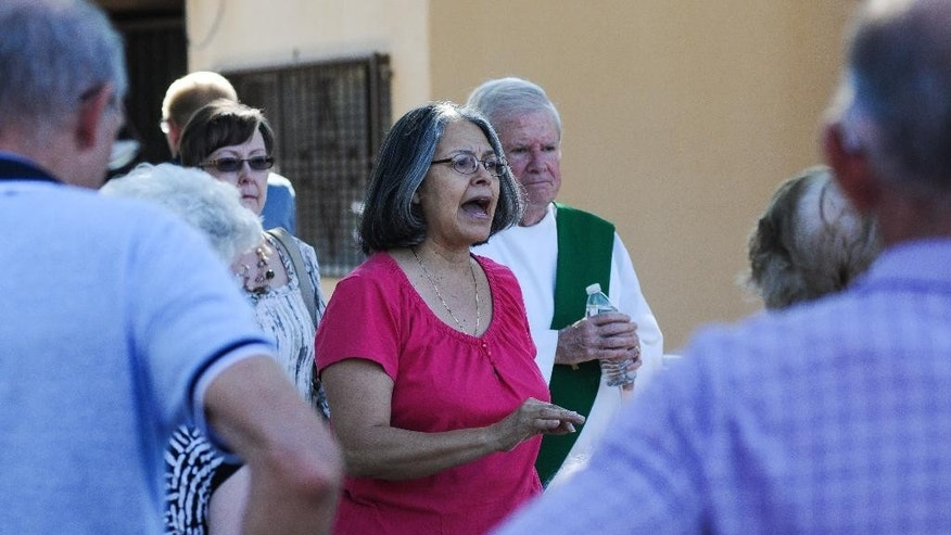 Holy Cross Catholic church pastoral associate Elizabeth Behnke informs parishioners of ride arrangements and that their cars must be left at the church until the parking lot is searched, on Sunday, Aug. 2, 2015 in Las Cruces, N.M. Churchgoers were left shaken during Sunday morning services after authorities say explosions occurred less than 30 minutes apart outside two Las Cruces churches. (Robin Zielinski/The Las Cruces Sun-News via AP) MANDATORY CREDIT