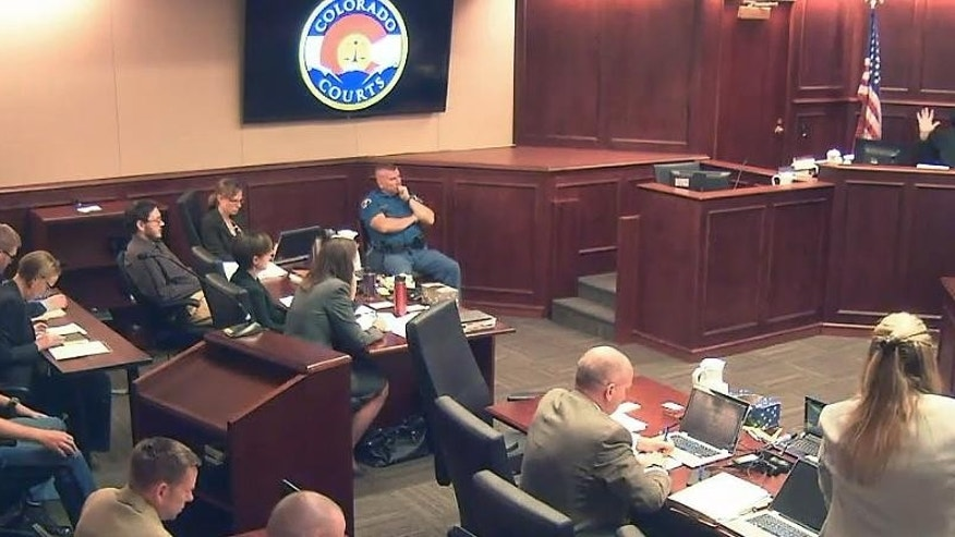 In this image made from Colorado Judicial Department video, Judge Carlos A. Samour Jr., top right, gestures during discussion with the prosecution's Lisa Teesch-Maguire, before bringing in the jury to begin penalty phase 3 in the trial of James Holmes, fifth from left in dark shirt, in Centennial, Colo., on Tuesday, Aug. 4, 2015. The jury in the Colorado theater shooting trial will hear even more heart-wrenching testimony from those who lost loved ones in the attack, as prosecutors begin their final push to have Holmes sentenced to death. (Colorado Judicial Department via AP, Pool)