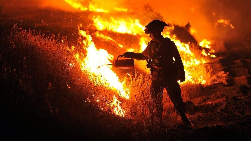 CalFire firefighter Bo Santiago lights a backfire as the Rocky fire burns near Clearlake, Calif., on Monday, Aug. 3, 2015. The fire has charred more than 60,000 acres and destroyed at least 24 residences. (AP Photo/Josh Edelson)