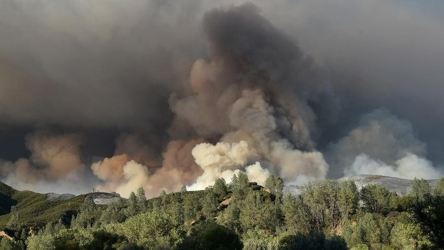 A plume of smoke rises above a hillside as the Rocky Fire burns near Clearlake, Calif., on Monday, Aug. 3, 2015. The fire has charred more than 60,000 acres and destroyed at least 24 residences. (AP Photo/Josh Edelson)
