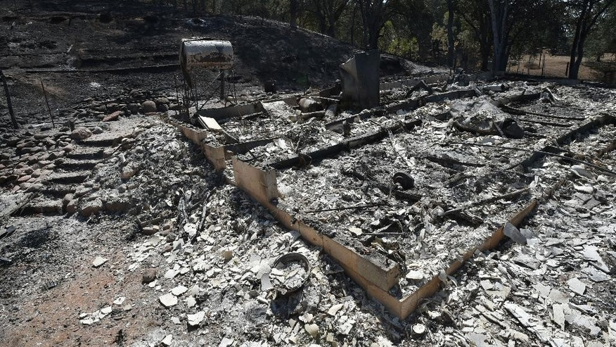 A burned out residence is seen as the Rocky fire burns near Clearlake, Calif., Monday, Aug. 3, 2015. Officials called for evacuations Monday as numerous homes were threatened by the flames. (AP Photo/Josh Edelson)