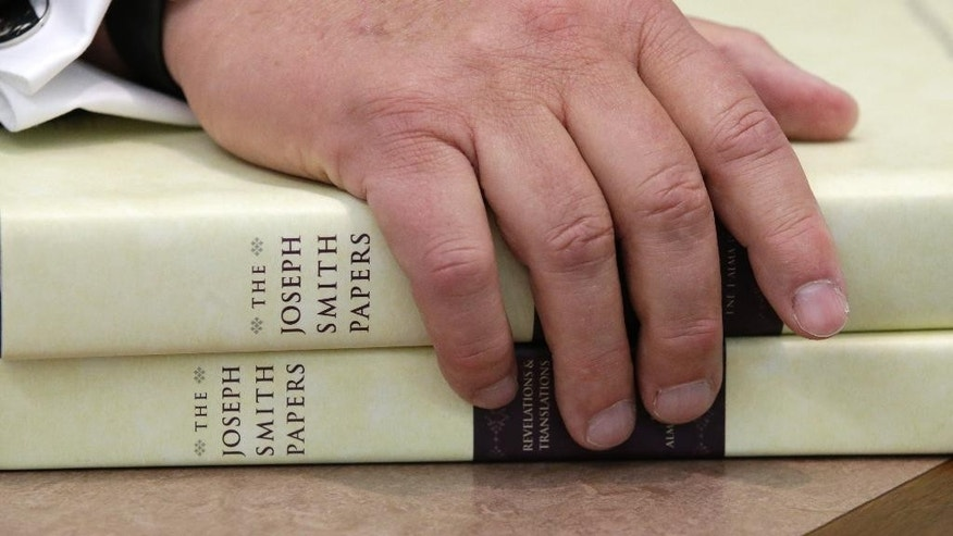 The Church of Jesus Christ of Latter-day Saints historian Steven E. Snow rests his hand on the third volume of the Joseph Smith papers, which includes the printer's manuscript of the Book of Mormon, during a news conference Tuesday, Aug. 4, 2015, in Salt Lake City. The Mormon church is taking another step in its push to be more transparent, and is releasing more historical documents that shed light on how Joseph Smith formed the religion. (AP Photo/Rick Bowmer)