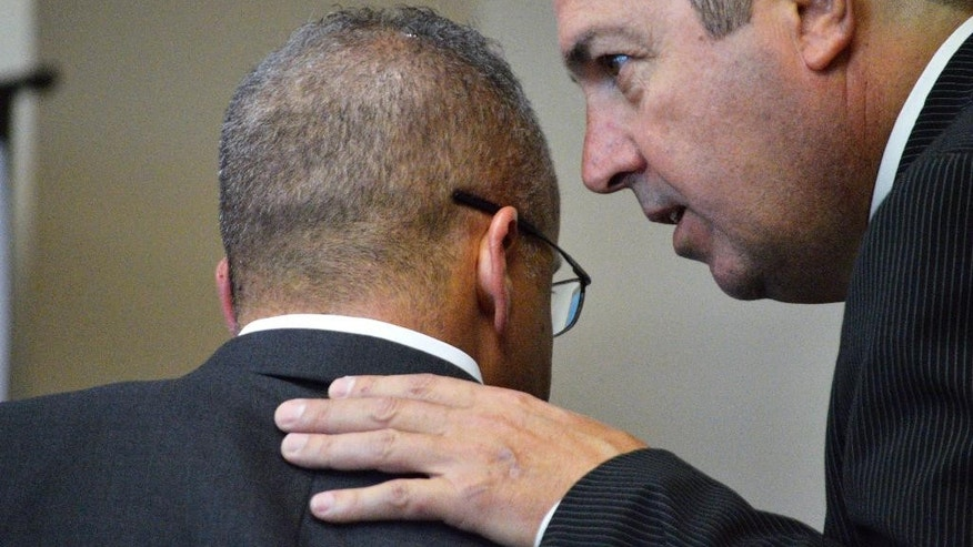 Defense attorneys Luis Robles, left, and Sam Bregman, right, confer during testimony at a preliminary hearing in Albuquerque, N.M. on Tuesday, Aug. 4, 2015, involving two officers facing murder charges. Former Albuquerque detective Keith Sandy and Albuquerque officer Dominique Perez are facing second-degree murder charges in the 2014 fatal shooting death of 38-year-old James Boyd. (AP Photo/Russell Contreras)