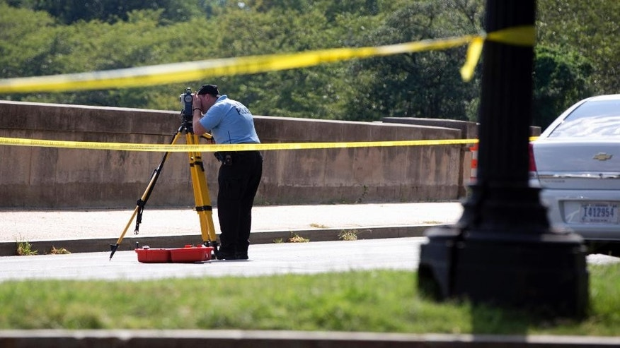 Members of the U.S. Park Police investigates the site of a reported shooting near the National Mall in Washington, Tuesday, Aug. 4, 2015. U.S. Park Police say they believe someone fired shots from a vehicle on the National Mal, a broad expanse of parkland in the heart of the U.S. capital.  (AP Photo/Carolyn Kaster)