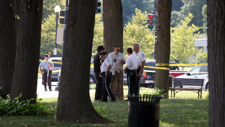 Law enforcement officers gather at the site of a reported shooting near the National Mall in Washington, Tuesday, Aug. 4, 2015. U.S. Park Police say they believe someone fired shots from a vehicle on the National Mal, a broad expanse of parkland in the heart of the U.S. capital.  (AP Photo/Carolyn Kaster)