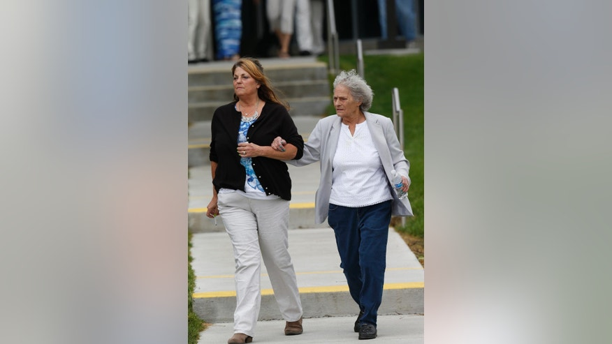 Rena Medek, left, walks out with an unidentified woman after the reading in penalty phase 2 in the trial of  James Holmes Monday, Aug. 3, 2015, in Centennial, Colo. Jurors declined to rule out death for Holmes as they moved toward sentencing the Colorado theater shooter.(AP Photo/David Zalubowski)