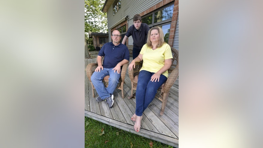 In this Wednesday, July 22, 2015, photo, Zach Anderson, center, and his parents, Les and Amanda Anderson, pose for a photo at their home in Elkhart, Ind. Zach and his parents are embroiled in a legal battle with a Niles, Mich., judge and prosecutor over sentencing on a charge that he had sex with a minor. (Dale G. Young/Detroit News via AP)