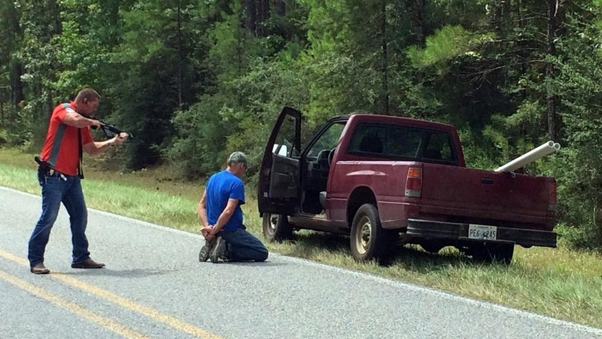 A Mississippi Bureau of Investigation agent detains a person of interest after shots were reportedly fired a second consecutive day near Camp Shelby, a military training facility near Hattiesburg, Miss., Wednesday, Aug. 5, 2015. There were no reported injuries. The description of the shooter was the same in both instances - a white male in a red pickup truck. (Ryan Moore/WDAM-TV via AP)