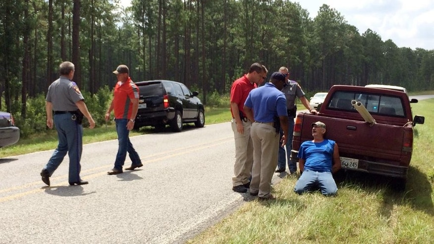 Mississippi Bureau of Investigation agents and state troopers detain a person of interest, right, after shots were reportedly fired a second consecutive day near Camp Shelby, a military training facility near Hattiesburg, Miss., Wednesday, Aug. 5, 2015. There were no reported injuries. The description of the shooter was the same in both instances - a white male in a red pickup truck. (Ryan Moore/WDAM-TV via AP)