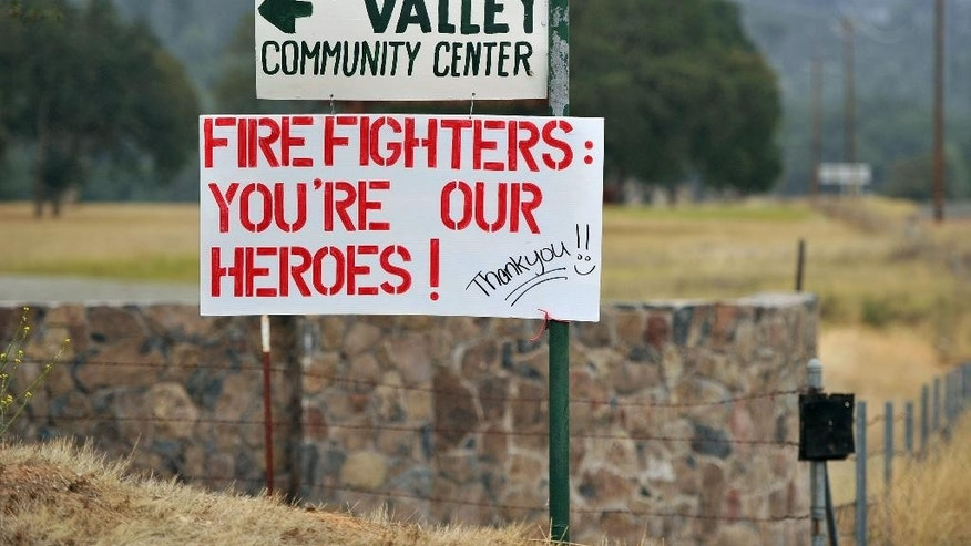 A sign showing support for firefighters is seen in Clearlake Oaks, Calif., on Tuesday, Aug. 4, 2015. The Rocky fire continues to burn and has charred more than 65,000 acres and destroyed 24 residences. (AP Photo/Josh Edelson)
