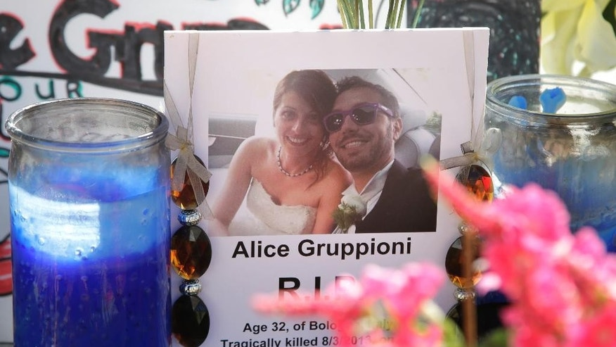 FILE - In this Aug. 5, 2013, file photo, a card showing the photo of Italian newlyweds Alice Gruppioni, left, and her husband Christian Casadei, is displayed on a memorial for Gruppioni along Ocean Front Walk at Venice Beach in Los Angeles. The driver who plowed through crowds on the tourist-packed Venice Beach boardwalk, killing Gruppioni, an Italian honeymooner and injuring 17 others two years ago, wants a new trial over claims of juror misconduct. Nathan Campbell, 40, was scheduled to be sentenced Wednesday, Aug. 5, 2015, in a Los Angeles courtroom for second-degree murder and other charges, but lawyers said it was likely to be postponed because of arguments for a new trial. (AP Photo/Jae C. Hong, File)