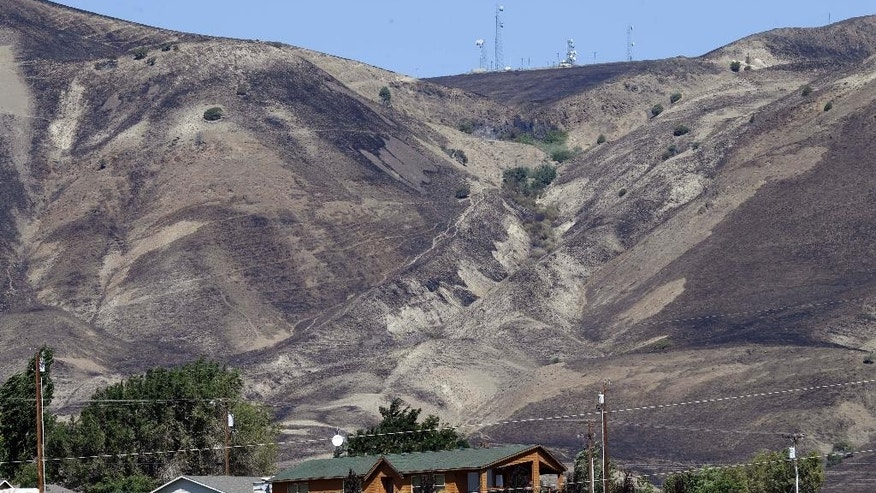Fire-blackened hills above a residence in Roosevelt, Wash., shows how close an early morning wildfire came to the town, Wednesday, Aug. 5, 2015.   Residents, who evacuated overnight, have returned to their homes and the fire is headed away for the town. (AP Photo/Don Ryan)