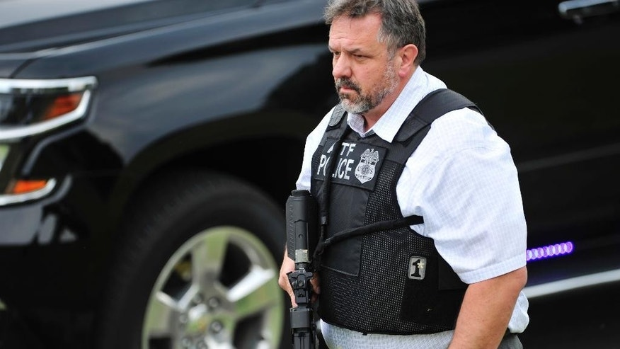 CORRECTS DATELINE TO ANTIOCH, NOT NASHVILLE - A police officer walks on the scene of a reported shooting in Antioch, Tenn., Wednesday, Aug. 5, 2015. A suspect wielding a hatchet and a gun inside a Nashville-area movie theater died after exchanging gunshots with a police team that stormed the theater, police said Wednesday. (John Partipilo/The Tennessean via AP) MANDATORY CREDIT NO SALES
