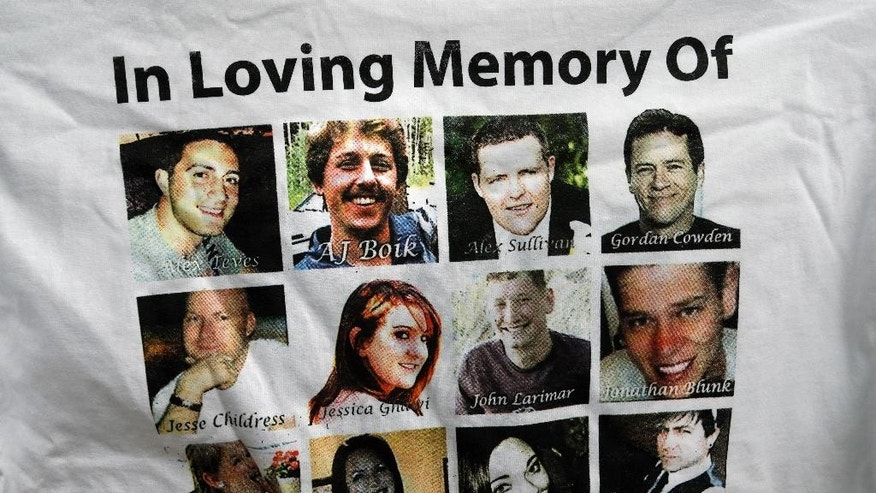 FILE - In this July 14, 2015, file photo, Sandy Phillips, whose daughter Jessica Ghawi  was killed in the 2012 Aurora movie theatre massacre, displays a T-shirt memorializing the twelve people killed in the attack, outside the Arapahoe County District Court following the day of closing arguments in the trial of theater shootings defendant James Holmes, in Centennial, Colo. Their names are, left to right, top to bottom row: Alex Teves, AJ Boik, Alex Sullivan, Gordon Cowden, Jesse Childress, Jessica Ghawi, John Larimer, Jonathan Blunk, Veronica Moser-Sullivan, Rebecca Wingo, Micayla Medek, and Matt McQuinn. (AP Photo/Brennan Linsley, File)