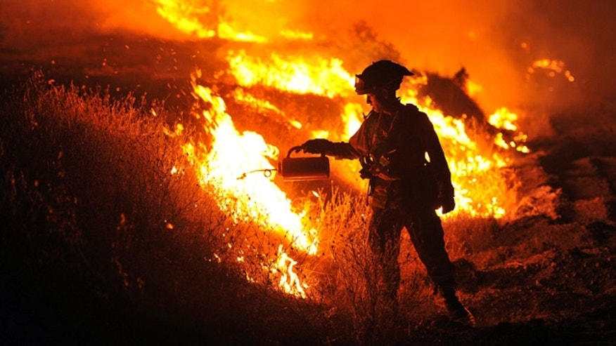 Aug. 3, 2015: CalFire firefighter Bo Santiago lights a backfire as the Rocky fire burns near Clearlake, Calif. The fire has charred more than 60,000 acres and destroyed at least 24 residences. (AP Photo/Josh Edelson)