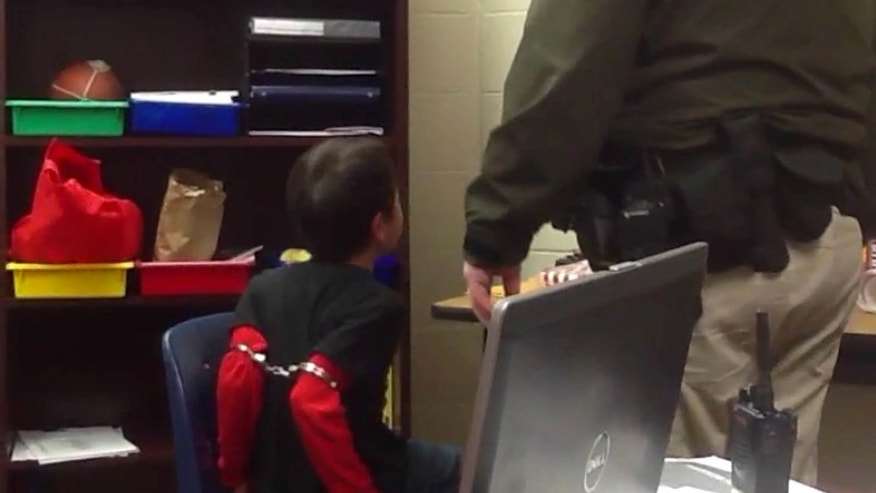 Aug. 4, 2015: In this image made from video taken in August 2014, and provided by the American Civil Liberties Union, an 8-year-old boy struggles and cries out as he sits in a chair with handcuffs around his biceps and his arms locked behind him while a school resource officer stands nearby, at an elementary school in Covington, Ky.
