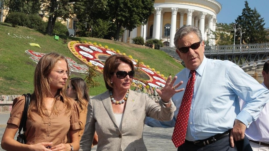Democratic leader and House Minority Leader Nancy Pelosi of Calif., center, flanked by her husband Paul Pelosi, right, talks as they stand in Independence Square, in Kiev, Ukraine, Wednesday, Aug 5, 2015.  The California democrat is leading a high-level congressional delegation on a trip to Ukraine. (AP Photo/Efrem Lukatsky)