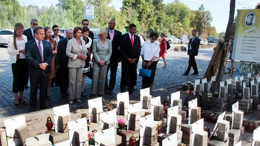 House Minority Leader Nancy Pelosi of Calif., and US delegation pay their respects to people killed in clashes with the police at a memorial in Independence Square, in Kiev, Ukraine, Wednesday, Aug 5, 2015.  The California democrat is leading a high-level congressional delegation on a trip to Ukraine. (AP Photo/Efrem Lukatsky)