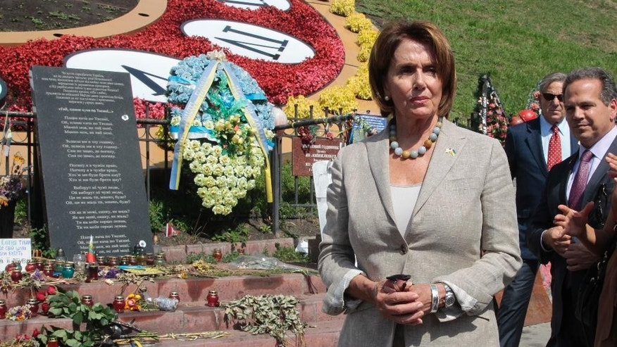 House Minority Leader Nancy Pelosi of Calif. lays flowers to pay her respect to people killed in clashes with the police at a memorial in  Independence Square, in Kiev, Ukraine, Wednesday, Aug 5, 2015.  The California democrat is leading a high-level congressional delegation on a trip to Ukraine. (AP Photo/Efrem Lukatsky)