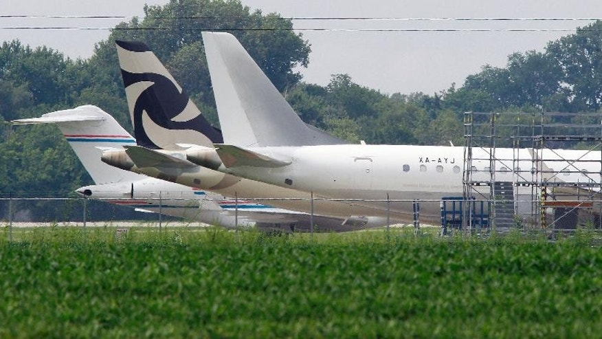 Jets are shown parked at St. Louis Downtown Airport in Sauget, Ill. on Wednesday Aug. 5, 2015. A woman talked her way past a security guard at the airport early Wednesday and entered the cockpit of a private plane before she was caught and taken to a hospital for observation for possible mental illness, authorities said.  (Tim Viser/Belleville News-Democrat via AP)\