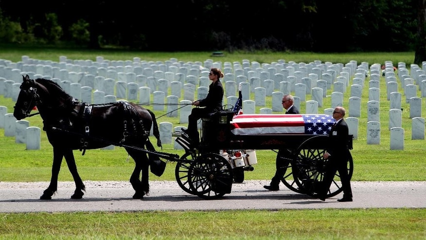 Memphis Police officer Sean Bolton's casket is carried by a horse drawn carriage at the West Tennessee Veterans Cemetery after his funeral Thursday, Aug. 6, 2015, in Memphis. Bolton was shot multiple times investigating an illegally parked car on Summerlane in Parkway Village on July 30. (Mike Brown/The Commercial Appeal via AP)