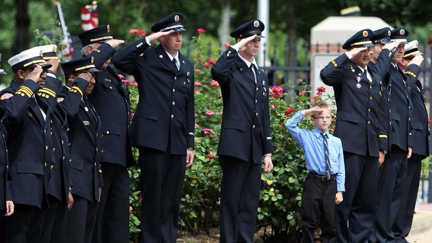 Colton Thornton, 6, stands with Memphis, Bartlett and Shelby County fire fighters and salutes as Memphis Police officer Sean Bolton's remains pass into West Tennessee Veterans Cemetery, Thursday, Aug. 6, 2015, after his funeral in Memphis. Bolton was shot multiple times investigating an illegally parked car on Summerlane in Parkway Village on July 30. (Mike Brown/The Commercial Appeal via AP)