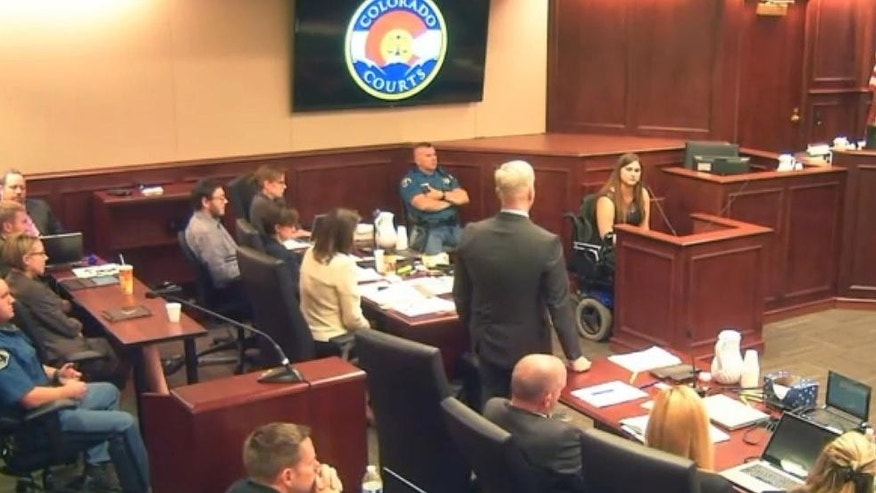 In this image taken from video, Ashley Moser, top right, whose daughter Veronica Moser-Sullivan, 6, was killed by James Holmes, who sits fifth from left in a gray shirt, testifies during the penalty phase of Holmes' trial in Centennial, Colo., Wednesday, Aug. 5, 2015. Prosecutor George Brauchler, center, questions Moser. (Colorado Judicial Department via AP, Pool)