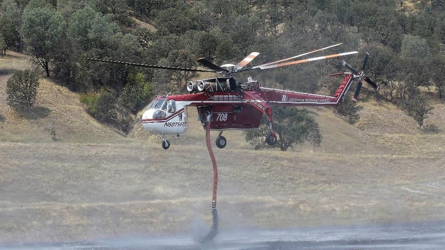 A firefighter works on putting out a hot spot near Clearlake, Calif., Wednesday, Aug. 5, 2015. Thousands of firefighters battling an unruly Northern California wildfire were aided overnight by cooler temperatures and higher humidity, but the fire is still less than a quarter contained. (AP Photo/Jeff Chiu)