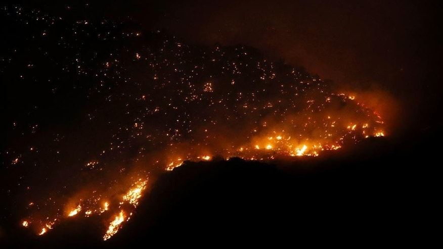 The Finger Rock Fire flares up with flames easily visible in Tucson and from a the northern end of Campbell Ave., Wednesday Aug. 5, 2015, near Tucson, Ariz. The wildfire re-ignited after lightning originally sparked it last Wednesday. (Kelly Presnell/Arizona Daily Star via AP)