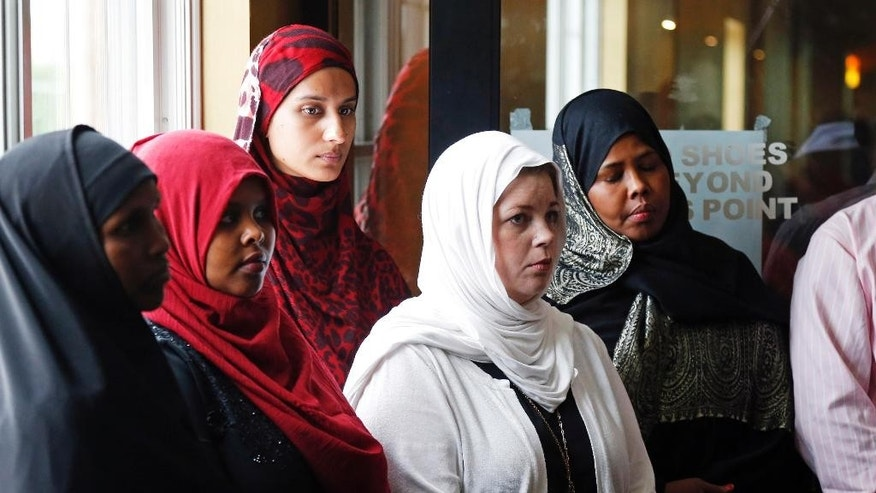 A group of women listen to Council on American-Islamic Relations-Minnesota Executive Director Jaylani Hussein, speaking about the Somali community concerns about the proposed government-initiated Countering Violent Extremism (CVE) program during a news conference, Thursday, Aug. 6, 2015, in Minneapolis. Muslim groups and civil rights activists across the nation are calling for greater transparency in the program by President Barack Obama's administration. (AP Photo/Jim Mone)