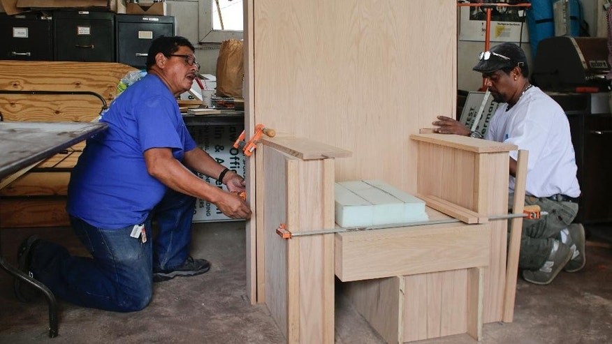 Fransisco Santamaria, left, and Fausto Hernandez, right, of Dominican Reublic build the papal chair which is being constructed by day laborers Thursday, Aug. 6, 2015, in Port Chester, N.Y. Pope Francis will use it when he celebrates Mass in Madison Square Garden this September. (AP Photo/Frank Franklin II)