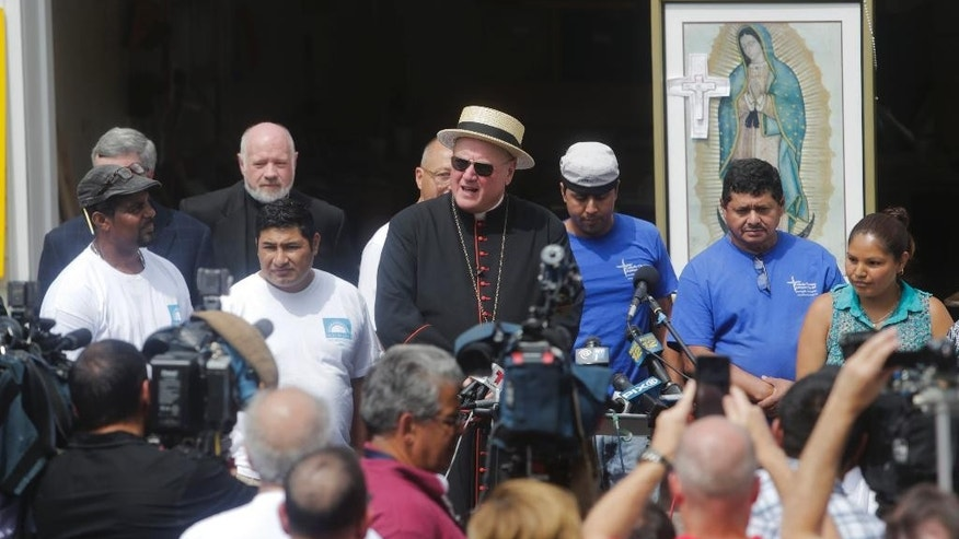 Cardinal Timothy Dolan, center, speaks a news conference where the papal chair that is being constructed by day laborers was made Thursday, Aug. 6, 2015, in Port Chester, N.Y. Pope Francis will use it when he celebrates Mass in Madison Square Garden this September. (AP Photo/Frank Franklin II)